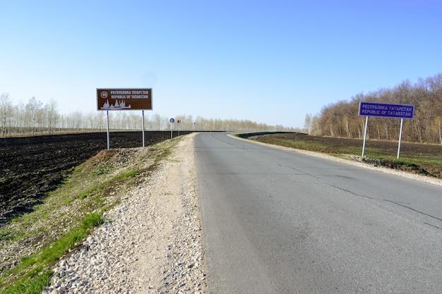 타타르스탄에 오신 것을 환영합니다. 시골도 타타르스탄 푯 말입니다. 맑고 푸른 하늘에 대 한 타타르스탄도로 표지판입니다. 아스팔트도로 클로즈업입니다.