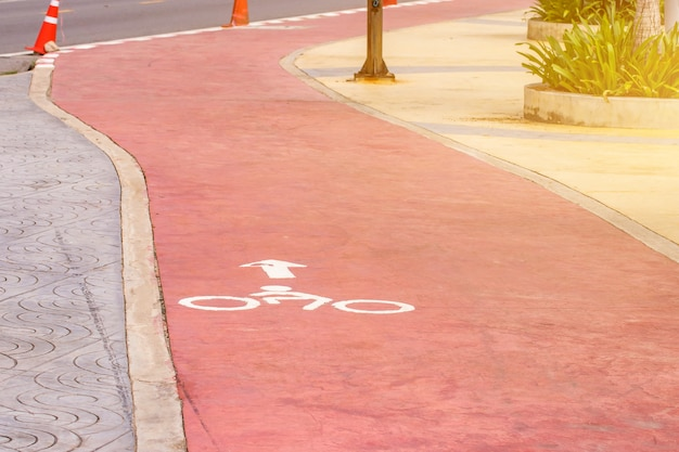 Sign of white cycling lane on red road track