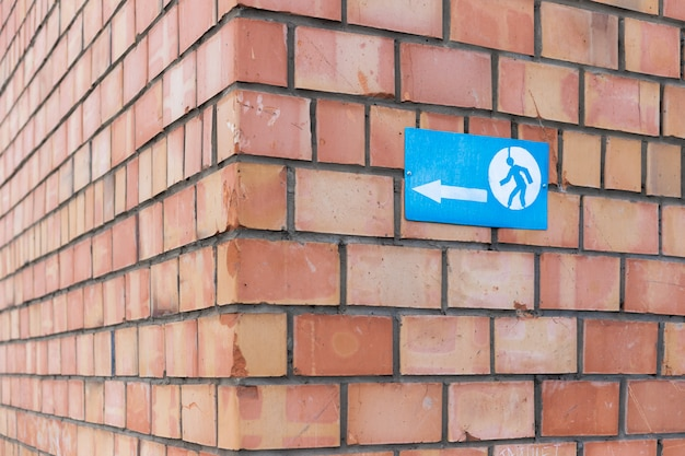 A sign with an arrow sign and a running man screwed to a brick wall. the sign indicates the corner of a brick building.