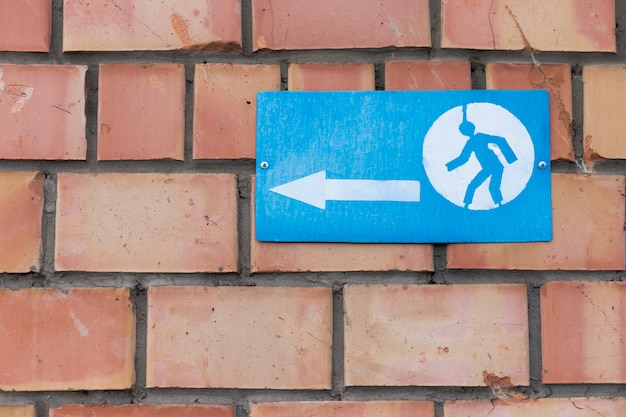 A sign with an arrow sign and a running man screwed to a brick wall.