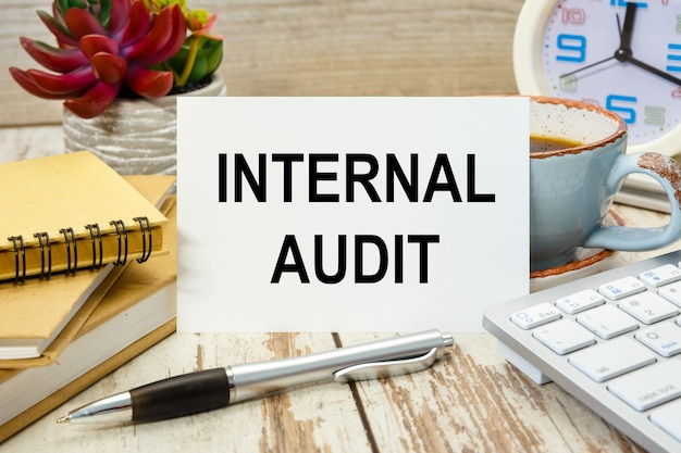 A sign with the inscription internal audit on the table with office supplies