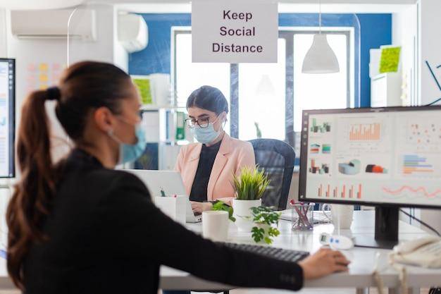 Подпишитесь, сохраняя социальное дистанцирование в новом обычном офисе во время глобальной пандемии между коллегами, ношение маски в качестве меры безопасности. женщина анализирует финансовую статистику на рабочем месте.