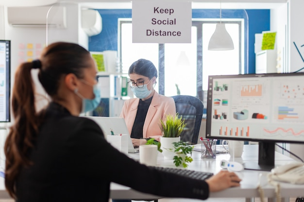 Sign with keep social distancing in new normal office during global pandemic between coworkers, wearing face mask as safety prevention. woman analyzing financial statistics in workplace.