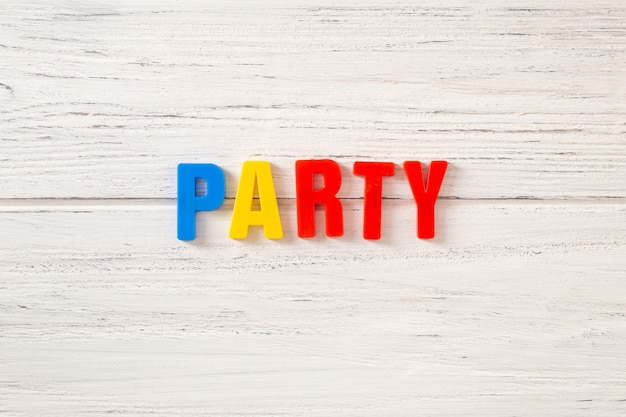 The sign, word party on a white wooden background, top view. children colored plastic letters.