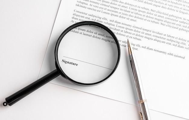 Линия подписи в контракте с ручкой и увеличительным стеклом