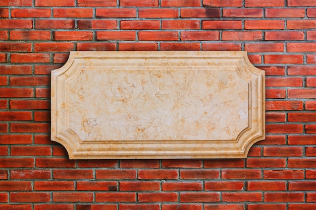 A signboard marble on brick wall.