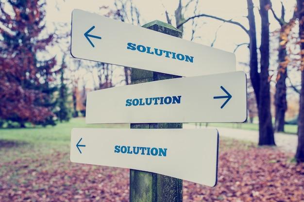 Вывеска со словом решение со стрелками, указывающими в трех направлениях