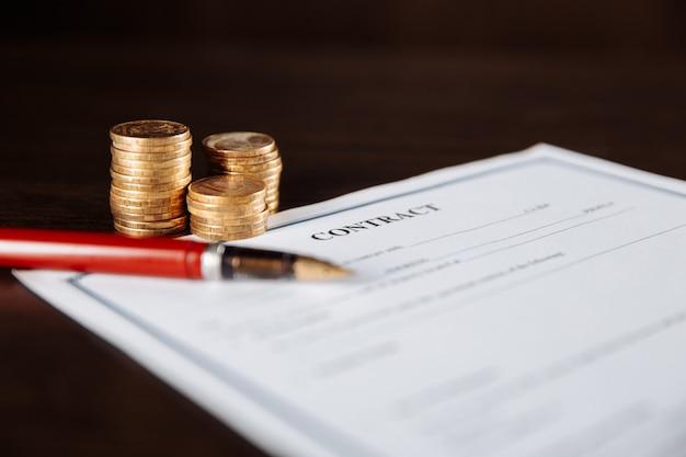 Подписание контракта, ручка и монеты на деревянном столе.