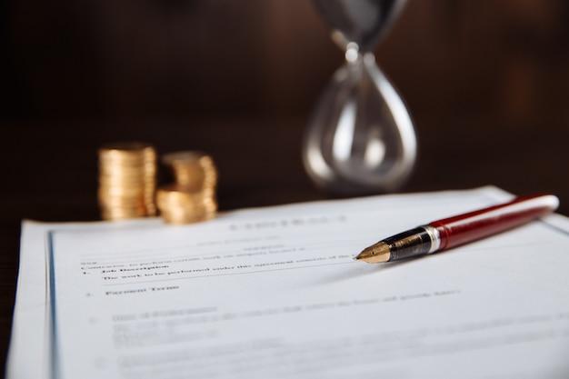 Подписание контракта, ручка, песочные часы и монеты на деревянном столе.