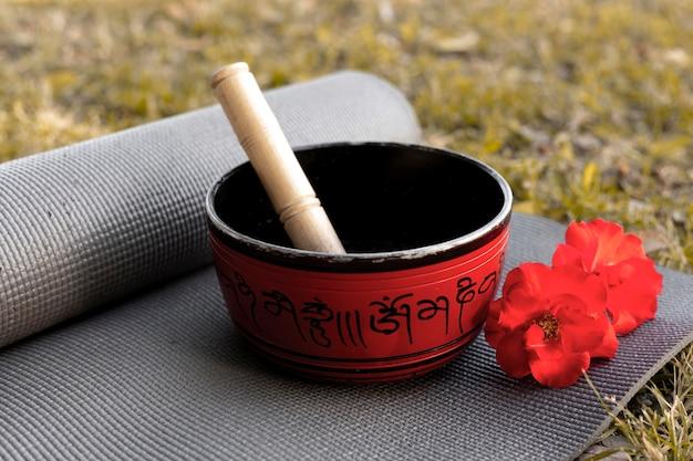 Подпись чаша с ковриком для йоги и цветами на траве