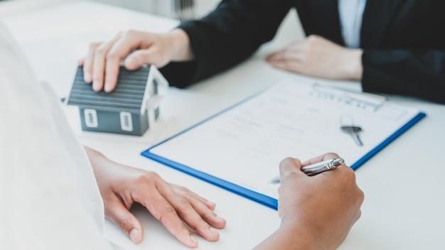 Подписание контракта после того, как агент по недвижимости объяснит покупателю коммерческий контракт или страхование жилья.