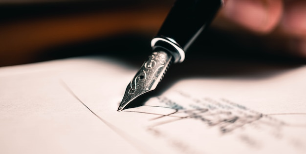 Signing the contract document with fountain pen, close-up shot.