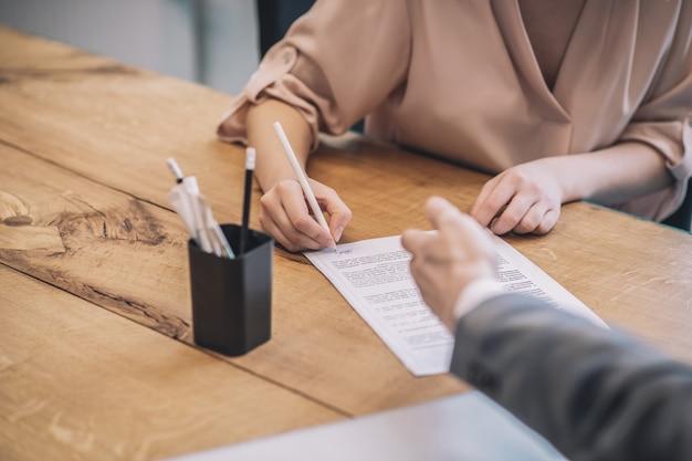 署名文書。オフィスのテーブルと男性のポインティング、顔なしで横たわっている薄い女性の手署名文書