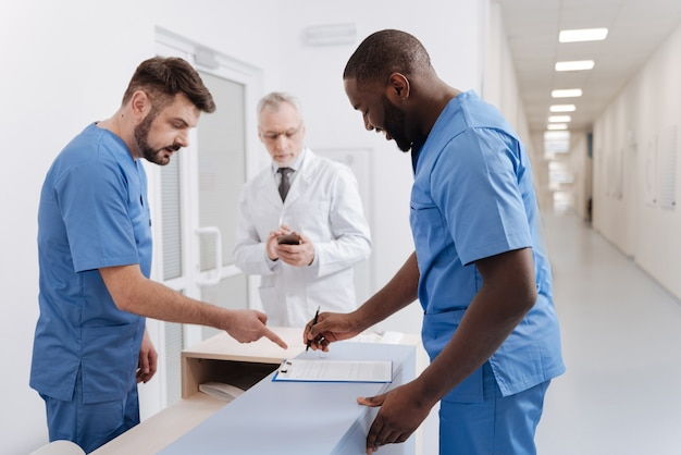 Signing important document . cheerful skilled diligent doctors working in the hospital and discussing diagnosis of the patient while aged colleague using phone in the background
