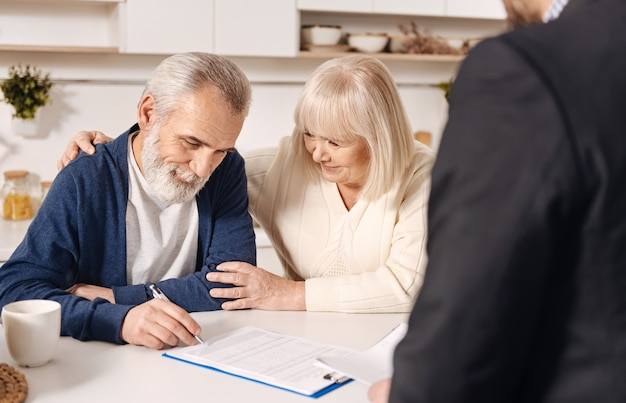 ローン契約に署名します。家に座って、書類に署名しながら不動産業者と会う魅力的な陽気な老夫婦の笑顔
