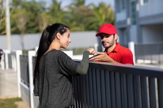 Подпись на смартфоне для получения посылки. красивая женщина получает пакет от доставщика в красной форме дома.