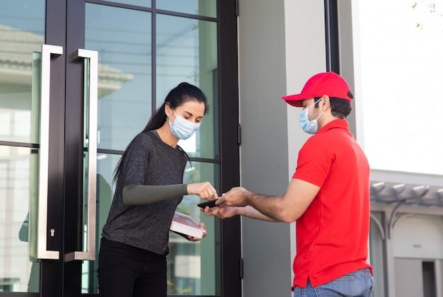 パッケージを取得するためにスマートフォンデバイスで署名に署名します。赤い制服を着た配達人から荷物を受け取る女性