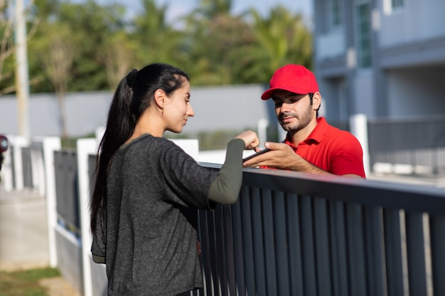 Signing signature on smart phone device to get a package. beautifu woman receiving package from delivery man in red uniform at home.