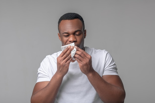 Signs of illness. unhappy young adult dark skinned man with handkerchief near nose with drooping eyelids and grimace