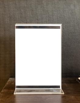 표지판은 나무 테이블에 아크릴 흰색 공백을 표시합니다.
