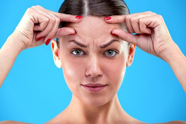 Признаки старения. портрет шокирован молодой женщины смотрит разочарованно, касаясь ее морщины на лбу на синей стене