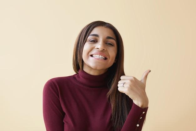 サイン、シンボル、ジェスチャーの概念。長くまっすぐな髪の陽気な若い混血の女性は、広く笑顔で、承認、尊敬、好みのサインとして親指を立てるジェスチャーを示しています