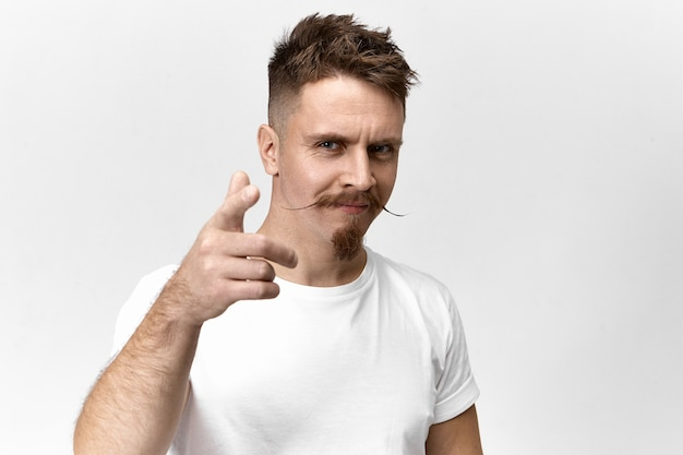 Signs, symbols, gestures and body language concept. horizontal view of confident joyful young handsome guy with trendy hairstyle, mustache and beard smiling and pointing fore finger at camera