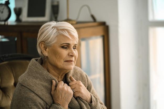 Задумчивая пожилая женщина, завернувшись в теплый свитер siiting на уютном диване