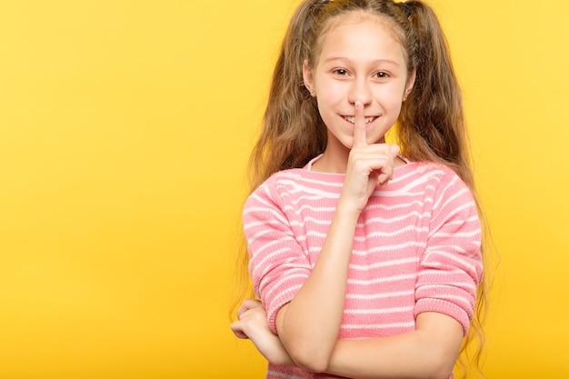 沈黙と静けさ。小さな女の子が視聴者を黙らせます。唇に指。表情。