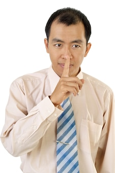 Silence sign with asian businessman finger near lips on white background.