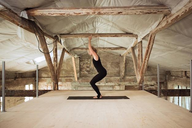 Silenzio. una giovane donna atletica esercita lo yoga su un edificio abbandonato. equilibrio della salute mentale e fisica. concetto di stile di vita sano, sport, attività, perdita di peso, concentrazione.