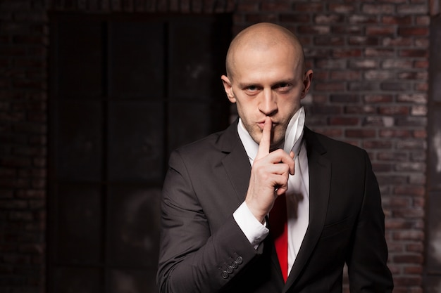 Silent killer explore oriental martial arts concept. bald contract murderer in suit and red tie holds combat knife. f