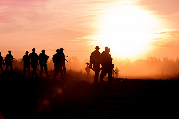 Silhouette action soldiers walking hold weapons is smoke and sunset and white balance ship effect dark art style