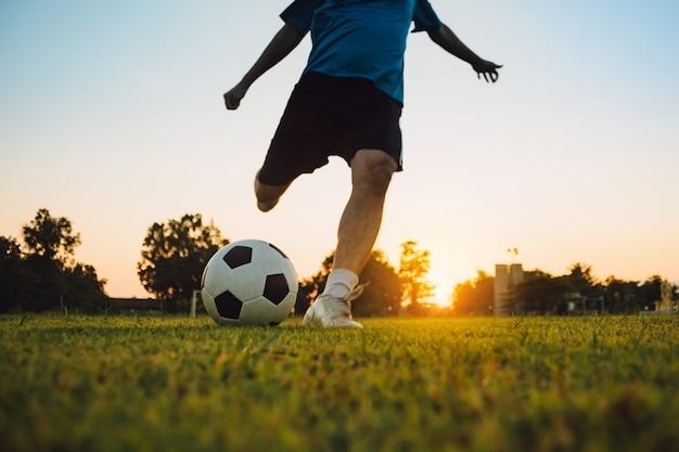 Силуэт действий спорта на открытом воздухе молодого человека, весело проводящего время, играя в футбол для упражнений на закате.