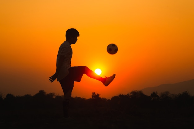 Silhouette action sport outdoors of a young man having fun playing soccer football for exercise under the sunset.