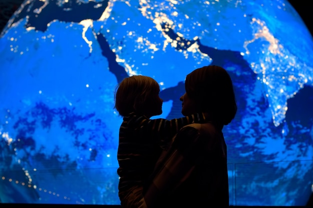 Silhouette of adult and child of globe earth