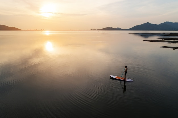Silhouette aerial view of stand up paddle boarder paddling at sunset on a flat warm quiet river.