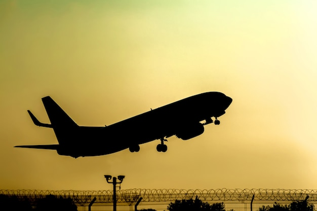 Silhouette of an airplane taking off at sunset