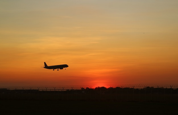 Silhouette of an airplane taking off up to the sunrise sky