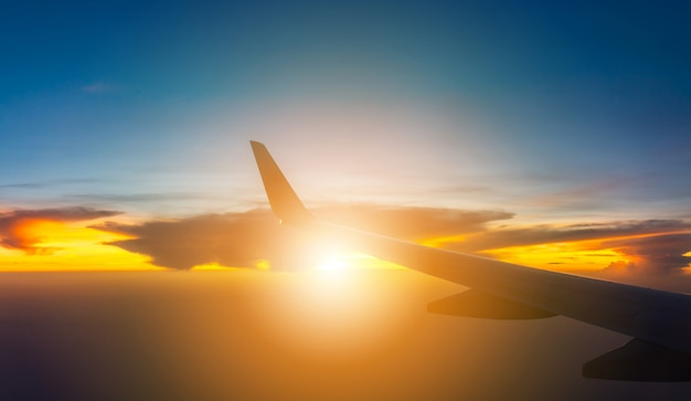 Silhouette of airplane wing view out of the window the cloudy sunset sky background, travel and holiday vacation concept