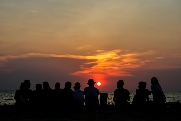 Silhouette all people in family meeting look sunset sky on beach