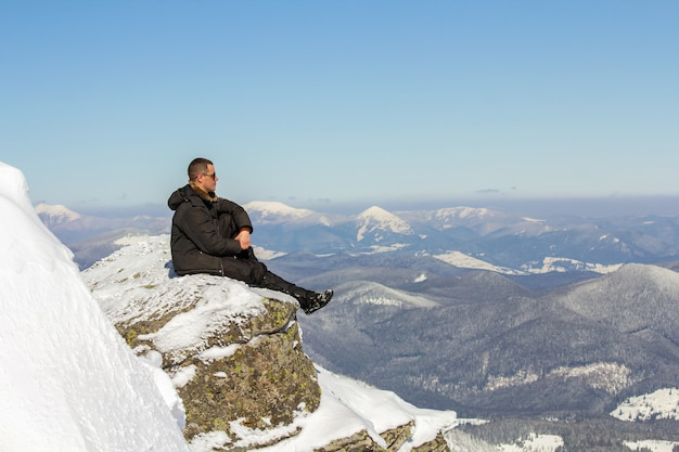 Silhouette of alone tourist sitting on snowy mountain top enjoying view and achievement on bright sunny winter day. adventure, outdoors activities, healthy lifestyle.