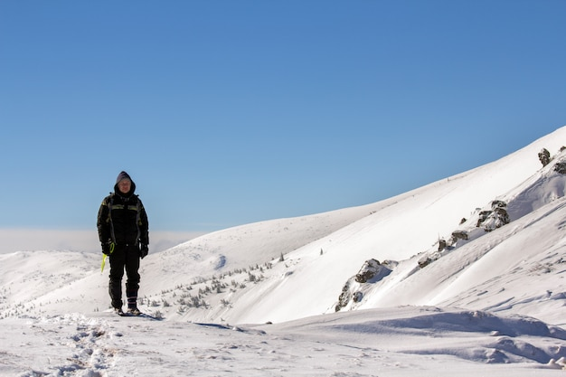 Silhouette of alone tourist standing on snowy mountain top enjoying view and achievement on bright sunny winter day. adventure, outdoors activities and healthy lifestyle concept.