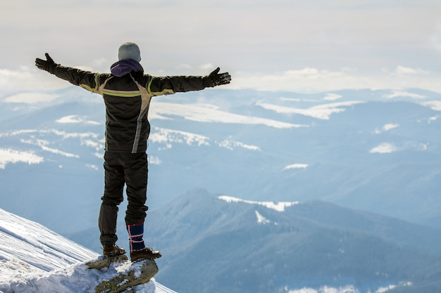Silhouette of alone tourist standing on snowy mountain top in winner pose