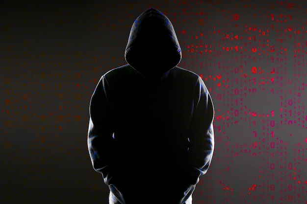 Silhouette of an anonymous hacker in the hood on the binary code