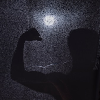 Silhouette of anonymous man flexing muscles
