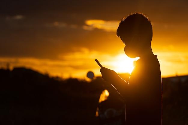 일몰에 스마트폰을 사용하는 실루엣 아시아 소년