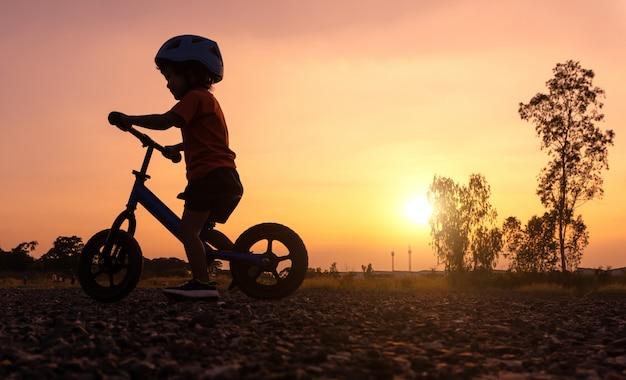 シルエットアジアの子供の初日はバランスバイクをプレイ。