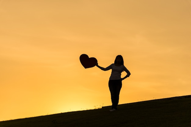 Silhouette of asian lady standing on hill and holding heart on the side during sunset time