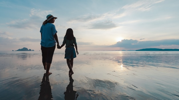 Silhouette of asian mother and daughter holding hand and walking on the beach together at the sunset time with beautiful sea and sky. family enjoy with nature concept.